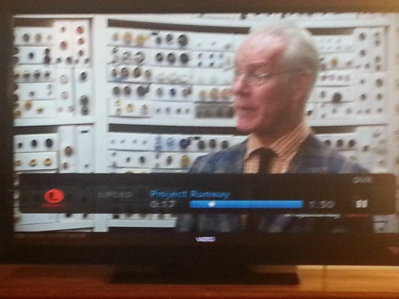 Tim Gunn in front of Mood's Wall of Buttons